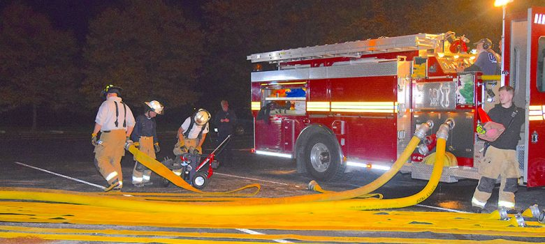 Image of firefighters/first responders, fire truck and hoses at night