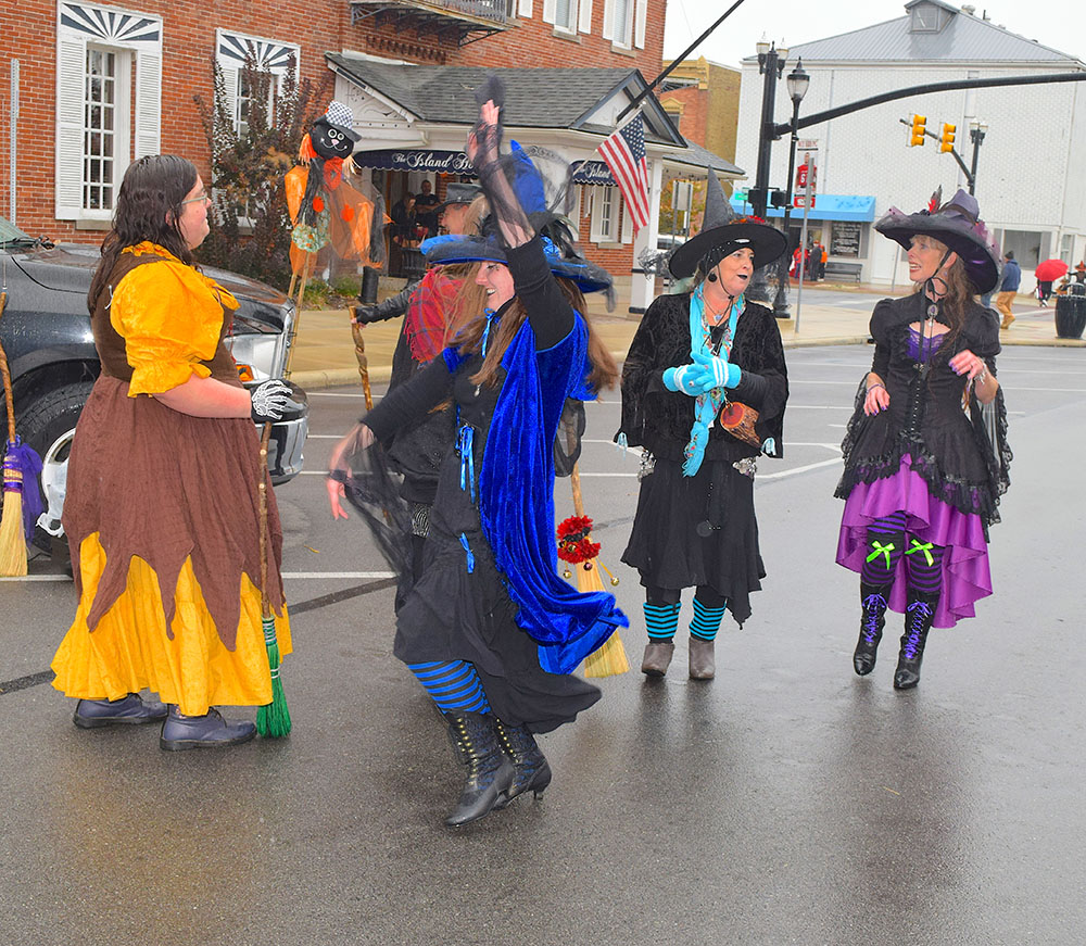 Women in witches costumes dance at Trunk-or-Treat event