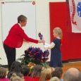 Principal handing a pinwheel to a student