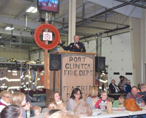 Lt. Trevor Johnson spins donation wheel at the Port Clinton Fire Department's annual Feather Party