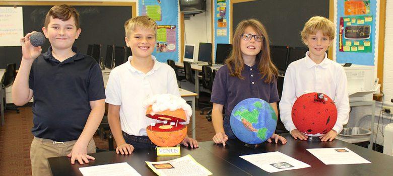 Students displaying homemade planets