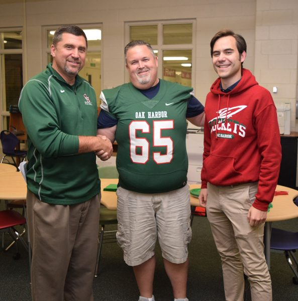 Port Clinton Mayor Mike Snider wears an Oak Harbor Rockets jersey while posing with Oak Harbor Mayor Mayor Quinton Babcock and Rocket's Coach Mike May