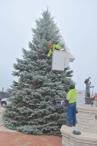 Two men decorate Port Clinton Christmas tree with lights, one in the bucket of a bucket truck toward the top
