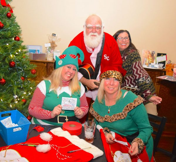 Santa's elves, Kelly Rigoni of Northern Exposure and Valerie Hoeber, under the watchful eye of the Singing Santa, J.D. Owen