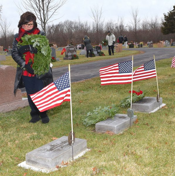 Woman stands before gravestone with wreath