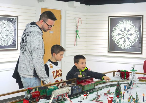 Image of man and children admiring a model train