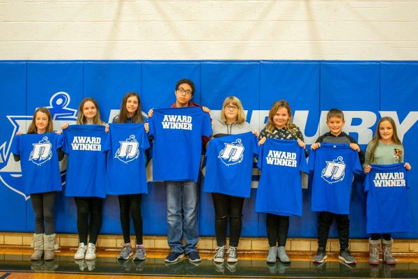 "Students hold shirts with Danbury logo on one side and ""Award Winner"" on the other"