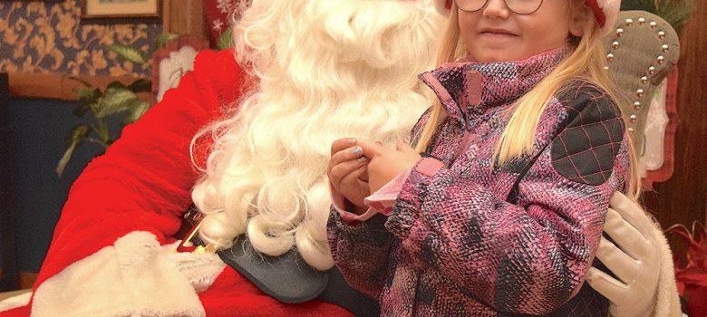 Santa Clause holding child at Port Clinton Community Christmas celebration