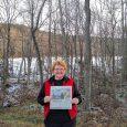 Image of Rita Koepfer holding a copy of The Beacon Massanutten, Va.