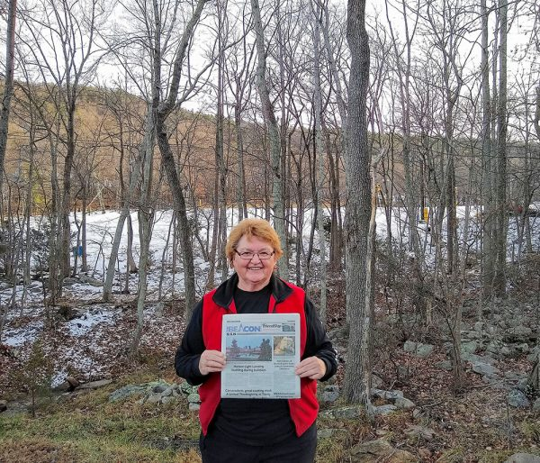 Image of Rita Koepfer holding a copy of The Beacon Massanutten, Va.