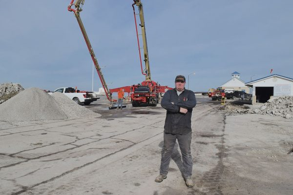 Image of Tim Niese Jr. in front of construction equipment