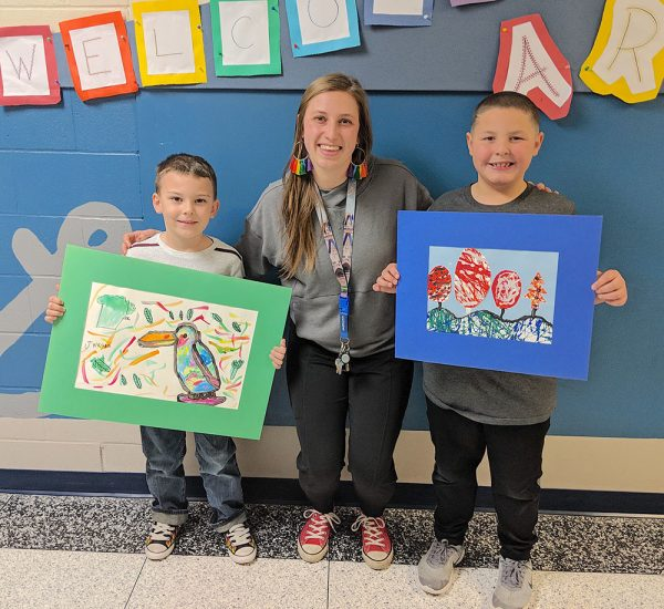 Image of Heather deHaas and Bataan Memorial students with artwork